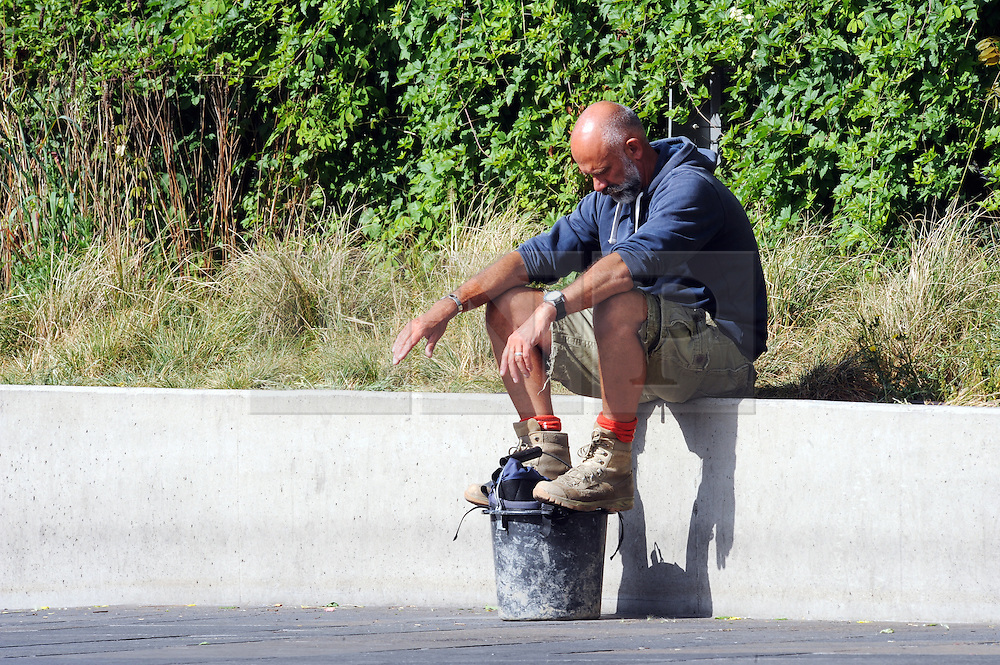 © Licensed to London News Pictures. 18/06/2015<br /> A workman waiting in the sun near the Cuttysark,Greenwich.<br /> Greenwich Sunny weather in South East London,UK.<br /> Early morning sunny weather in Greenwich Village and Greenwich Park today (18,06,2015)<br /> (Byline:Grant Falvey/LNP)