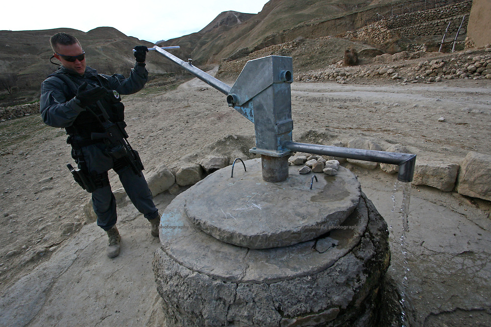 A german police officer checks the recent condition of a newly established well in the Marmal mountain range near Mazar-e Sharif.