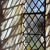 Detail of stone-framed church window with diamond-leaded panes of clear or pale yellow grass throwing interesting shadows