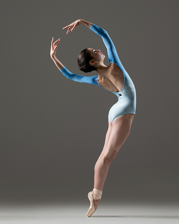 Classical female ballet dancer, Arianna Spitz, in a dip dye blue leotard in the photo studio on a grey background. Photograph taken in New York City by photographer Rachel Neville.