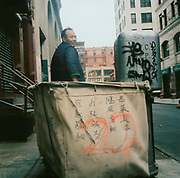 Asian man weeling a laundry basket in the street USA