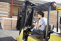 Forklift Driver by Loading Dock Moving Stack of Lumber