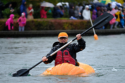 A man prepares to race giant pumpkins across Lake of the Commons at the 14th annual West Coast Giant Pumpkin Regatta in Tualatin, Ore. on October 21, 2017. (Photo by Alex Milan Tracy)