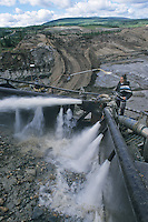 Mine worker extracts gold using jets of water. This process is called monitoring. Dawson City Yukon, gold mine.