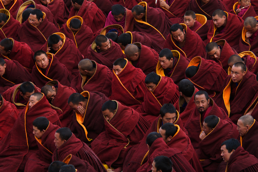 Buddhist Gelugpa monks wearing heavy maroon robes congregate outside the main prayer hall of Labrang Monastery, for Losar prayers, at Tibet's New Year.<br /> <br /> Each day during Losar thousands of pilgrims walk the kora around the monastery, which is lined with prayer wheels.<br /> <br /> Established in 1709, Labrang housed over 4000 monks at its peak, but now only has around 1500 monks.