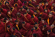 Buddhist Gelugpa monks wearing heavy maroon robes congregate outside the main prayer hall of Labrang Monastery, for Losar prayers, at Tibet's New Year.<br />