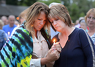 Christine Martucci, left, and Barbara Young-Martucci of Frenchtown, New Jersey reflect as names of victims are read during a candlelight vigil in support of the victims of the Orlando massacre Monday, June 13, 2016 in New Hope, Pennsylvania.   (Photo by William Thomas Cain)