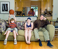 Family of five in suburban living room early evening