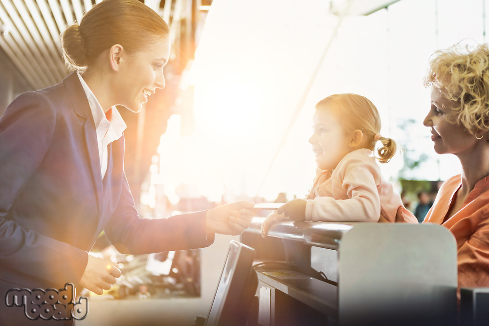 Portrait of mature woman carrying her cute little child while she is giving her passport with lens flare in airport