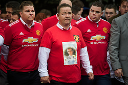 © Licensed to London News Pictures. 26/10/2017. Epsom, UK. Mourners wearing Manchester United shirts and a picture of Tom Doherty at the Funeral of Tom 'Tomboy' Doherty the nephew of Big Fat Gypsy Weddings star Paddy Doherty, at Epsom Cemetery in Epsom, Surrey. Tom Doherty was 17 when he was killed in a car crash in South Nutfield in Surrey on October 9. He had passed his driving test just days earlier. Photo credit: Ben Cawthra/LNP