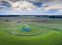 © Licensed to London News Pictures. 20/06/2020. Amesbury, UK. A small crowd (R) watches as the Summer Solstice sun sets on the longest day of the year over Stonehenge in Wiltshire. The ancient stone circle remains closed to visitors because of social distancing rules during the pandemic. Sunrise and sunset have been live streamed. Photo credit: Peter Macdiarmid/LNP