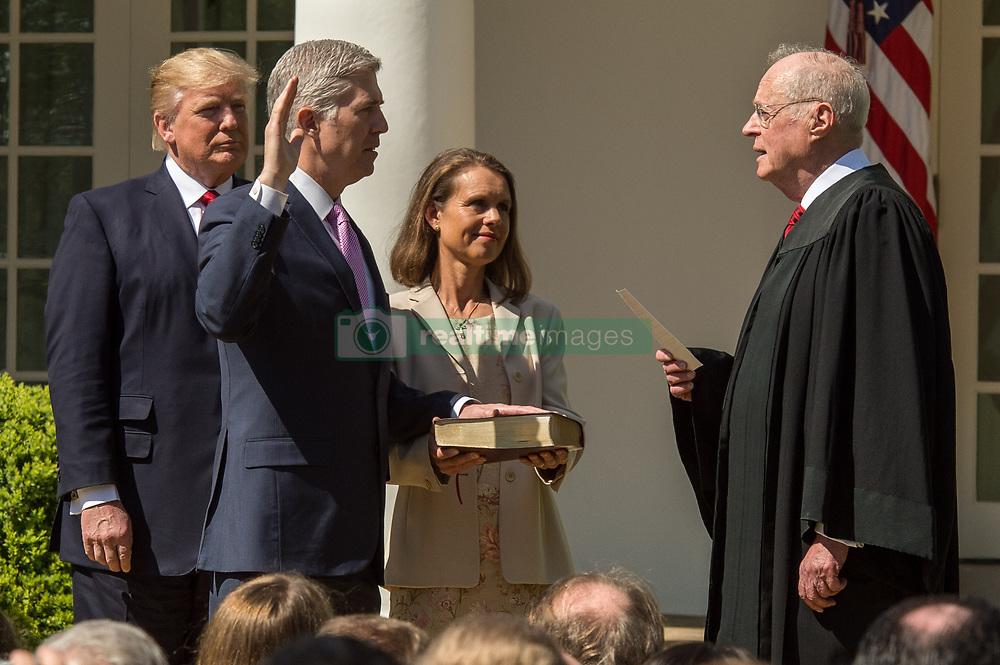 April 10, 2017 - Washington, District of Columbia, U.S. - The Honorable NEIL GORSUCH, second left, is sworn in by Supreme Court Justice ANTHONY KENNEDY, right, while Gorsuch's wife LOUISE GORSUCH and President DONALD TRUMP looking on in the Rose Garden of the White House. (Credit Image: © Ken Cedeno via ZUMA Wire)