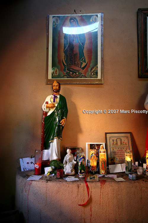 SHOT 12/26/2007 - Religious figures and candles in the Our Lady of Guadalupe Chapel in Old Town Albuquerque. Albuquerque is the largest city in the state of New Mexico, United States. It is the county seat of Bernalillo County and is situated in the central part of the state, straddling the Rio Grande. The city population was 448,607 as of the 2000 U.S. census. As of the 2006 census estimate, the city's population was 504,949, with a metropolitan population of 816,811 as of July 1, 2006. In 2006, Albuquerque ranked as the 33rd-largest city and 61st-largest metropolitan area in the U.S. Albuquerque is home to the University of New Mexico (UNM) and Kirtland Air Force Base as well as Sandia National Laboratories and Petroglyph National Monument. The Sandia Mountains run along the eastern side of Albuquerque and the Rio Grande flows through the city north to south..(Photo by Marc Piscotty/ © 2007)
