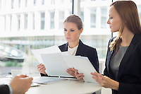 Businesswomen discussing over documents in office cafeteria