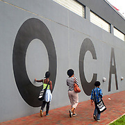 Visitors to MOCA (Museum of Contemporary Art) in North Miami walk past the MOCA sign. The museum's new building was opened in 1996 and was designed by Charles Gwarthmey.(Photo by Edeline Mezinord)