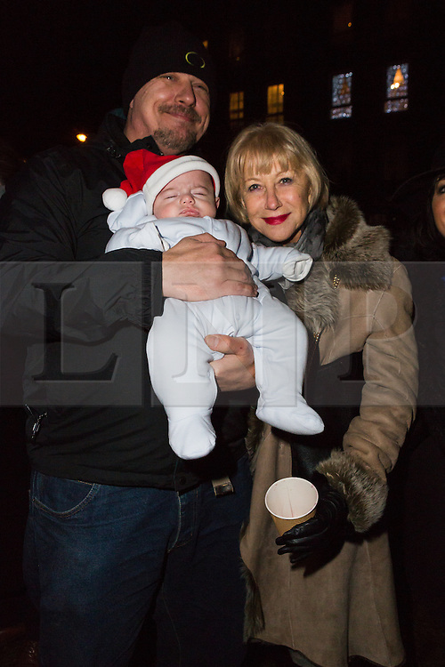 © Licensed to London News Pictures. 08/12/2014. London, UK. Helen Mirren poses for a photograph with a baby wearing a santa hat. Dame Helen Mirren turns on the Christmas tree lights at Wapping Green in Tower Hamlets, East London tonight. This is the first time in many years that Wapping has had a Christmas tree and Dame Helen Mirren surprised residents by turning up at the community event and leading the countdown to switching the tree lights on. She then joined residents singing carols and drinking mulled wine, at the event which was arranged by the local councillor for Wapping and St Katharines, Julia Dockerill. Photo credit : Vickie Flores/LNP