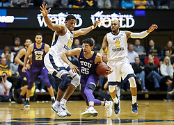 Feb 12, 2018; Morgantown, WV, USA; West Virginia Mountaineers forward Sagaba Konate (50) and West Virginia Mountaineers guard Jevon Carter (2) trap TCU Horned Frogs guard Alex Robinson (25) during the second half at WVU Coliseum. Mandatory Credit: Ben Queen-USA TODAY Sports