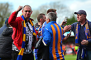 Shrewsbury fans celebrate at full time on the pitch during the Sky Bet League 2 match between Cheltenham Town and Shrewsbury Town at Whaddon Road, Cheltenham, England on 25 April 2015. Photo by Alan Franklin.