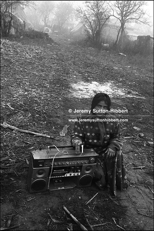GIRL IN POSE THAT SHE CHOSE FOR PHOTOGRAPH. SINTESTI, ROMANIA. NOVEMBER 1996..©JEREMY SUTTON-HIBBERT 2000..TEL./FAX. +44-141-649-2912..TEL. +44-7831-138817.