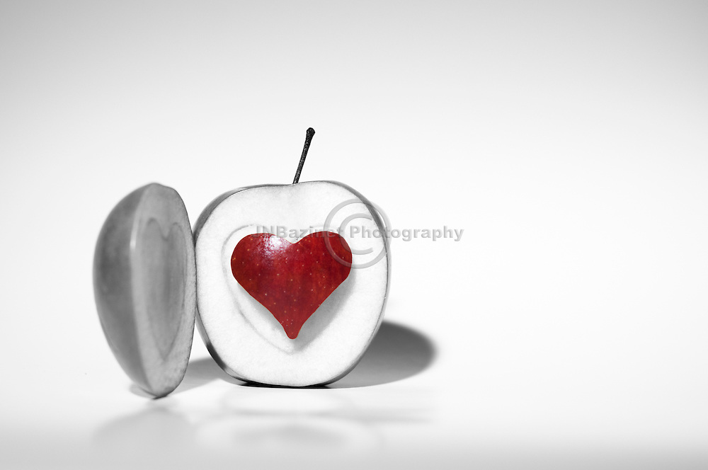 Black and white image of green apple with heart-shaped apple core in bold, vivd red.