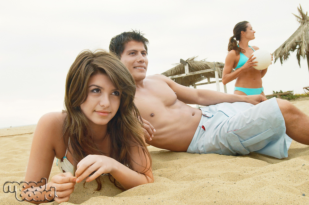 Couple Lying on Sand by Friend with Volleyball