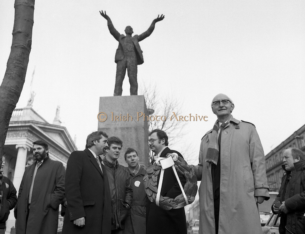 Workers Party Commemoration Of James Larkin.(R50)..1987..07.02.1987..02.07.1987..7th February 1987..A wreath laying ceremony was held today at the memorial for Trade Union leader,James Larkin. The ceremony was conducted the Workers' Party. Mr Tomás McGiolla, leader of the Workers'Party, laid the wreath at the memorial in O'Connell Street, Dublin. The ceremony was held to commomerate the 40th anniversary of the death of James Larkin...Image shows Mr McGiolla holding wreath at the monument in O'Connell Street. Include in the photograph are Clrs, E Byrne, Eamon Gilmore, Mike Jennings and Pat Rabitte.Also included is Prionsíos DeRossa (L)