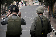 Israeli soldiers face a crowd of Palestinian youths during clashes in the West Bank city of Hebron, Monday, Feb. 22, 2010. Palestinians clashed with Israeli troops in Hebron amid outrage over Israel's plan to restore two flashpoint Jewish holy sites in the occupied territory.