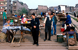 CHINA SICHUAN PROVINCE FENGDU MAY99 - Chinese men descend on stairs crammed with hawkers at the shore of the Yangtse river. Seven large cities and thousands of villages will be submerged once the water level rises after the completion of the controversial Three Gorges Dam project further downriver. The flooding of areas reaching back more than 550Km upriver will require the evacuation and resettlement of more than 10 million people.  jre/Photo by Jiri Rezac. © Jiri Rezac 1999. . Contact: +44 (0) 7050 110 417. Mobile:  +44 (0) 7801 337 683. Office:  +44 (0) 20 8968 9635. . Email:   jiri@jirirezac.com. Web:     www.jirirezac.com