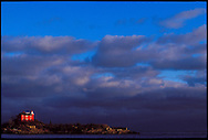 THE MARQUETTE LIGHTHOUSE LIT BY THE RISING SUN UNDER STORM CLOUDS ON LAKE SUPERIOR IN MARQUETTE MICHIGAN.