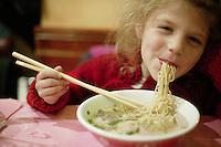 January 2004, Paris, France --- Girl Eating Chinese Noodle Soup --- Image by © Owen Franken/Corbis