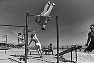 People practice bodyweight exercise in Brooklyn, New York, April 18, 2016. Bodyweight exercises are strength training exercises that do not require free weights or machines as the individual's own weight provides resistance against gravity.