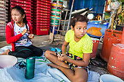30 APRIL 2013 - MAHACHAI, SAMUT SAKHON, THAILAND:   Burmese girls work in a Thai fishing net workshop in Mahachai, Samut Sakhon province, Thailand. The Thai fishing industry is heavily reliant on Burmese and Cambodian migrants. Burmese migrants crew many of the fishing boats that sail out of Samut Sakhon and staff many of the fish processing plants in Samut Sakhon, about 45 miles south of Bangkok. Migrants pay as much $700 (US) each to be smuggled from the Burmese border to Samut Sakhon for jobs that pay less than $5.00 (US) per day. There have also been reports that some Burmese workers are abused and held in slavery like conditions in the Thai fishing industry.         PHOTO BY JACK KURTZ