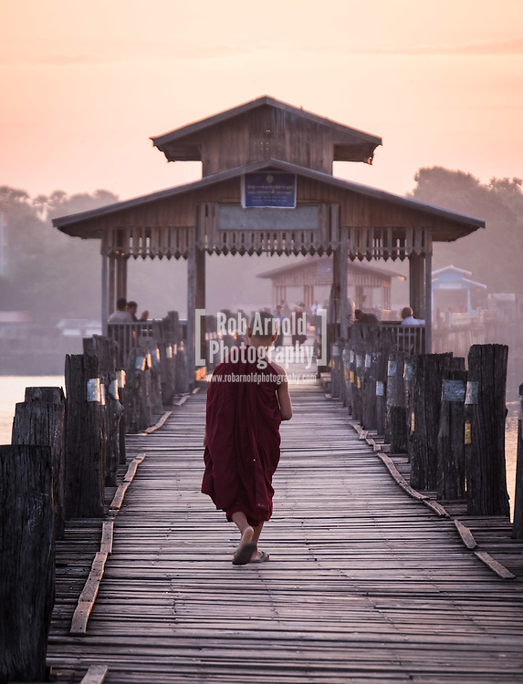A young novice monk walks at sunrise across the wooden U Bein's Bridge near Amapura in Mandalay.