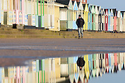 © Licensed to London News Pictures. 30/11/2013. Southwold, UK A man walks near deserted beach huts reflected in seawater. Crashing waves on the seafront in Southwold, Suffolk today, 30 November 2013. Photo credit : Stephen Simpson/LNP