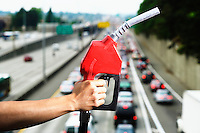 Hand holding a gas pump nozzle overlooking rush hour traffic on Interstate 5 from a highway overpass.