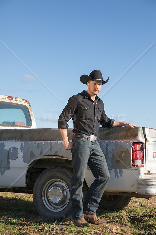 cowboy leaning against a vintage pickup truck