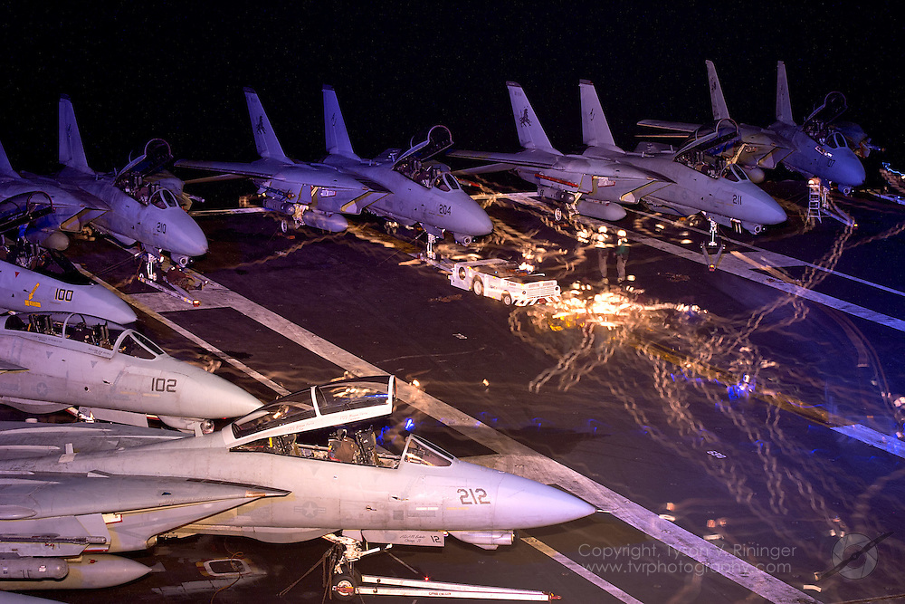 Aircraft handlers scurry about the flight deck during this long exposure image taken late at night somewhere in the Atlantic aboard the deck of the USS Theodore Roosevelt CVN-71 during sea trials prior to their 2005 Mediterranean deployment. This would be the final cruise for the F-14 Tomcat and the last time it would ever see combat.