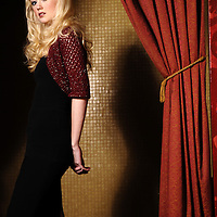 A young blonde woman standing beside a curtain