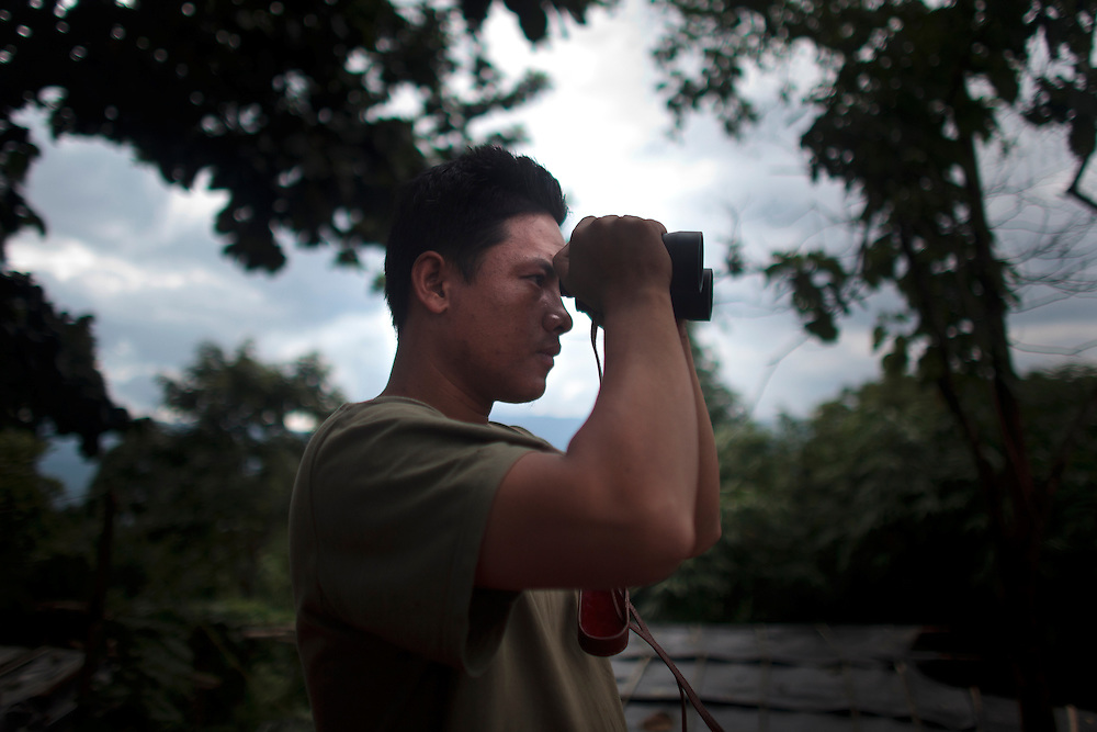 A KIA's soldier use a binoculars to watch the enemy camp in the Naw HPyu Post in the front line of the war against the Burma Government, Myanmar on August 3, 2012. The KIA formed in 1961 in response to a military coup in Burma led by General Ne Win, who attempted to consolidate Burmese control over regions on the periphery of the state which were home to various ethnic groups. From 1961 until 1994, the KIA fought a grueling and inconclusive war against the Burmese junta. In 2011, general Sumlut Gun Maw confirmed renewed fighting in the state of Kachin for independence. One of the new reasons for the ending of the ceasefire is the creation of the Myitsone Dam which requires the submergence of dozens of villages in Kachin state.