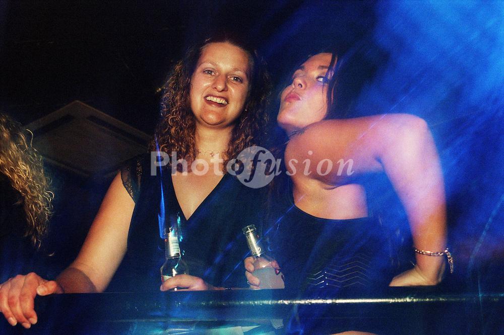 Teenage girls standing in nightclub holding bottles of alcohol,