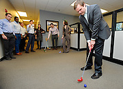Insight Sourcing Group's Mike O'Brien putts a golf ball toward the cup on an indoor putting course during a happy hour event Friday, Feb. 27, 2015, in Norcross, Ga. The company is one of Atlanta's top businesses according to the firm's own employees. David Tulis / AJC Special