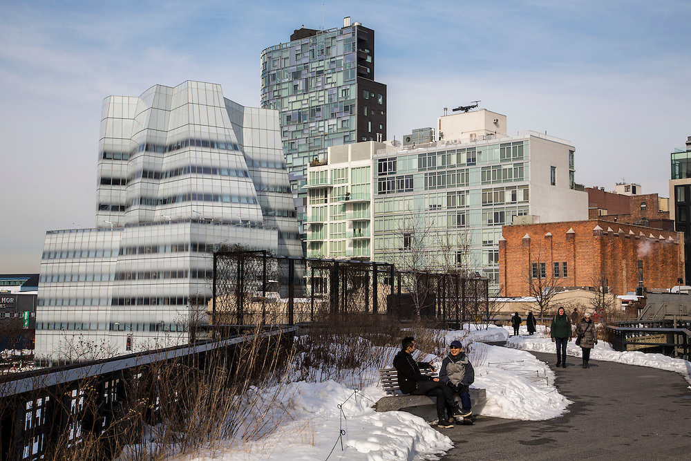 Two people sit and talk on a bench surrounded by snow on the High Line walkway over 10th Avenue; Chelsea; New York City; New York, United States of America.  The iconic InterAtiveCorp building is in the background.  (photo by Andrew Aitchison / In pictures via Getty Images)