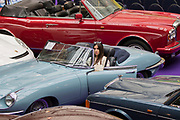 UNITED KINGDOM, London: 24 April 2018 Maria, from Greece, takes a closer look at a 1969 Jaguar E-Type Series II 4.2 Roadster (approx £70,000 - 80,000). The car forms part of the Spring Classics: An Important Auction of Fine Historic Automobiles at The Royal Horticultural Halls, Westminster. The auction will see a collection of privately owned cars be auctioned this evening April 24th 2018. Rick Findler  / Story Picture Agency