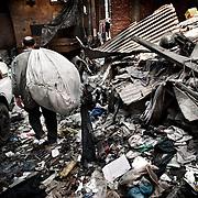 """Qualquier rincón de una calle de Mokattam sirve como almacén de los desperdicios recolectados. En medio del barrio de Manshiet Nasr a las afueras de El Cairo esta situado el asentamiento de Mokattam conocido como la """"Ciudad de la Basura"""" , está habitado por los Zabbaleen ,una comunidad de unos 45.000 cristianos coptos que viven desde hace varias décadas de reciclar los desperdicios que genera la capital egipcia: plástico, aluminio, papel y desechos órganicos que transforman en compost . La mayoría forman parte de la Asociación para la Protección del Ambiente (APE) una ONG que actúa en el área, cuyos objetivos son proteger el medio ambiente y aumentar el sustento de las recuperadores de basura de El Cairo. Según la ONU, el trabajo que se realiza en Mokattam como uno de los diez mejores ejemplos del mundo en el mejoramiento medioambiental. El Cairo , Egipto, Junio 2011. ( Foto : Jordi Camí )"""