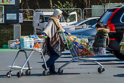 A shopper leaves using two trollies, but neither are overloaded - Coronavirus (Covid 19) warnings mean shops are short of toilet rolls and dry foods but although queues are long people dont appear to be over buying, in general.