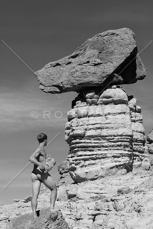 sexy nude man with a rock near a rock formation in New Mexico