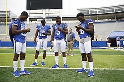 Kentucky running back Shihiem King, left, wide receiver Jeff Badet, running back Jojo Kemp and running back Stanley Williams are engrossed in their phones during the University of Kentucky's annual media day, Friday, Aug. 07, 2015 at Commonwealth Stadium in Lexington.