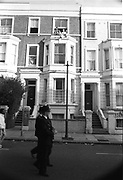 Policemen walking through a street and people looking out of their window from the top floor of a house, Notting Hill Carnival, London, 1989