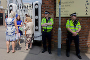 Women chat at a side entrance next to officers from Thames Valley police helping with security during the annual Royal Ascot horseracing festival in Berkshire, England. Royal Ascot is one of Europe's most famous race meetings, and dates back to 1711. Queen Elizabeth and various members of the British Royal Family attend. Held every June, it's one of the main dates on the English sporting calendar and summer social season. Over 300,000 people make the annual visit to Berkshire during Royal Ascot week, making this Europe's best-attended race meeting with over £3m prize money to be won.