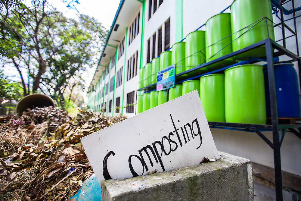 CAPTION: Ten students from Parang High school recently attended a climate change workshop that was run by the local government and facilitated by ACCCRN's implementing partners, ICLEI. Since attending the workshop, the students have become more active around their school, encouraging their peers to participate in climate change-related initiatives such as segregating organic waste for composting. Behind the composting heap is a rainwater harvesting system, which was installed by Marikina City Government. During heavy rain, water will be captured in these barrels and used for watering plants, flushing toilets and washing, reducing the school's water bills and also its dependence on mains water. Rainwater harvesting has been identified by the local government as a good climate resilience building initiative, and it plans to replicate this across other schools in the city. LOCATION: Parang High School, Marikina City, Philippines. INDIVIDUAL(S) PHOTOGRAPHED: N/A.